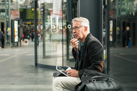 Senior male commuter talking through in-ear headphones while sitting by bags at railroad station - MASF08529