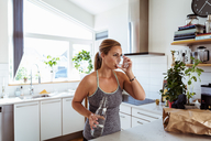 Tired woman in sports clothing drinking water while standing at kitchen - MASF08541