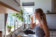 Side view of woman in sports clothing drinking water at kitchen - MASF08544