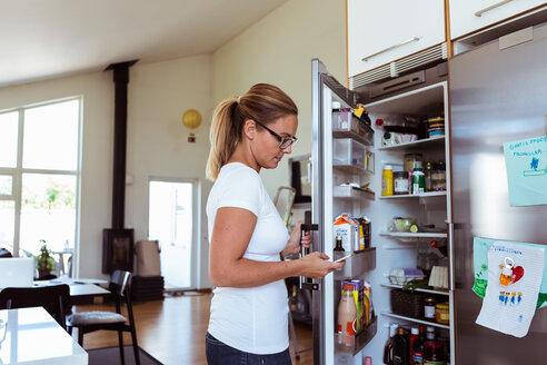 Side view of woman using mobile phone while standing by open refrigerator at kitchen - MASF08550