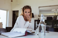Tensed woman looking at bills while sitting at table in living room - MASF08553