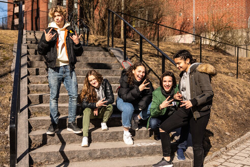Cheerful multi-ethnic teenage friends gesturing on steps in city - MASF08559