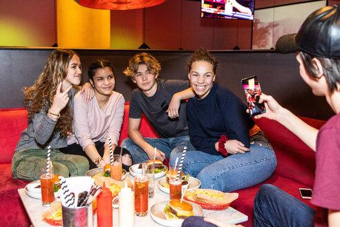 Teenage boy photographing multi-ethnic friends sitting on sofa at restaurant - MASF08562