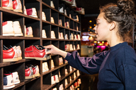 Side view of teenage girl holding bowling shoes at wooden rack - MASF08574