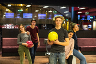 Portrait of smiling teenage boy holding ball while standing against friends at bowling alley - MASF08577