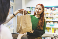 Smiling customer receiving paper bag from shop assistant in a cosmetics shop - WPEF00666