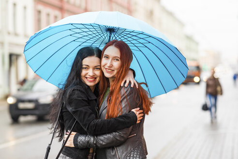 Two happy women hugging in the city on a rainy day - WPEF00675