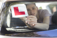 Learner driver placing letter L on rear window of car - ZEF15779