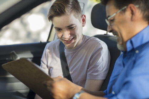 Learner driver with instructor in car looking at test script - ZEF15794
