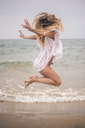 Happy young woman jumping on the beach - ACPF00099