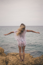 Rear view of young woman standing with outstretched arms on a rock at the coast - ACPF00108