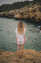 Rear view of young woman standing on a rock at the coast - ACPF00111
