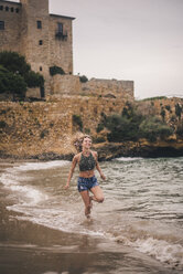 Happy young woman running on the beach - ACPF00117