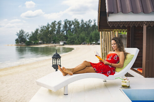 Thailand, Koh Phangan, smiling woman reading book on terrace beside the beach - MOMF00469
