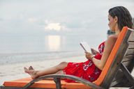 Thailand, Koh Phangan, woman sitting on sunlounger on the beach using digital tablet - MOMF00481