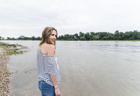 Smiling woman standing at the riverside - UUF14447