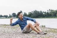 Laughing man sitting at the riverside throwing stones - UUF14459