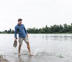 Smiling man splashing water in a river - UUF14462