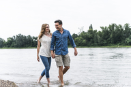 Smiling couple wading in river - UUF14465