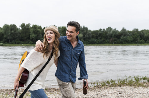 Happy couple walking at the riverside with beer bottle and guitar - UUF14495