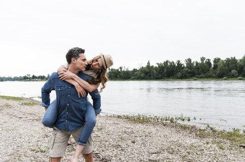 Man carrying girlfriend piggyback at the riverside - UUF14498