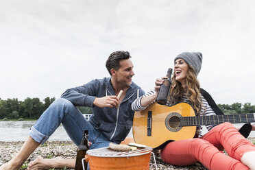 Happy couple with beer bottle, guitar and grill relaxing at the riverside - UUF14507