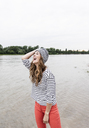 Laughing woman wearing wooly hat at a river - UUF14516