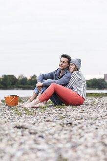 Affectionate couple sitting at the riverside - UUF14522