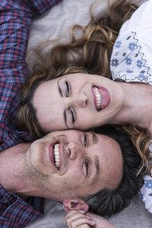 Happy playful couple lying on a blanket - UUF14531