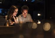 Smiling couple having dinner looking at laptop - UUF14543