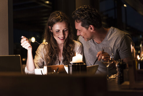 Smiling couple having dinner together - UUF14549