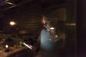 Man leaning at the window in a dark illuminated room using cell phone - UUF14552
