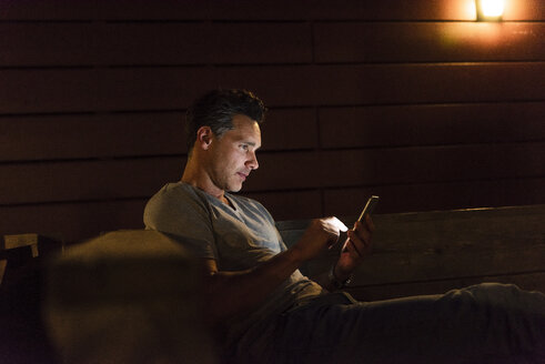Man sitting in a dark illuminated room using cell phone - UUF14555