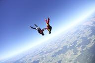 Female skydivers upside down above Leutkirch, Bavaria, Germany - CUF40375