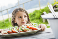 Young girl holding salad plate for picnic lunch, Tyrol, Austria - CUF40384
