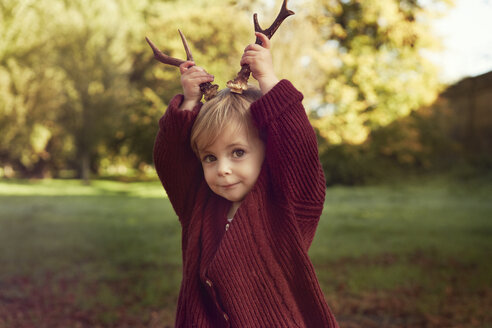 Toddler using sticks as antlers - CUF40429