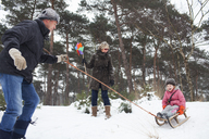 Father and grandmother pulling girl on toboggan in snow - CUF40441