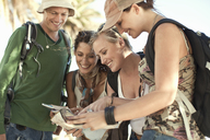 Four young adult friends looking at map, Cape Town, South Africa - CUF40474