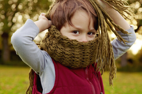 Boy in park, with scarf covering mouth - CUF40526