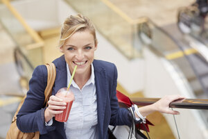 Businesswoman on escalator with shopping and fruit drink - CUF40544