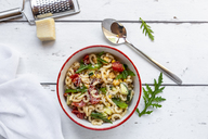 Bowl of noodle salad with corn, cucumber, tomatoes, rocket and grated parmesan - SARF03824