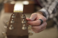 Close-up of man's hand tuning guitar - ZEF15817