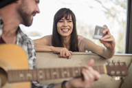 Young man at home playing guitar and woman taking a selfie - ZEF15826