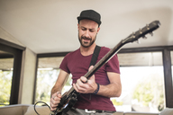 Passionate young man playing electric guitar in living room at home - ZEF15829