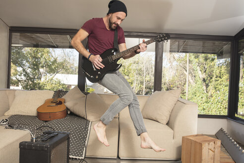 Passionate young man playing electric guitar in living room at home jumpimg arund - ZEF15832