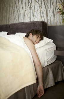 Young man lying in bed - CUF40570
