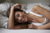 Smiling woman laying on bed - CUF40738