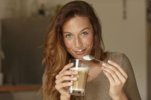 Smiling woman eating coffee foam - CUF40741