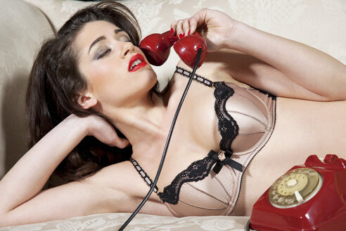 Woman in lingerie talking on phone - CUF40858