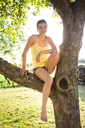 Portrait of smiling girl sitting barefoot on tree in summer - LVF07252